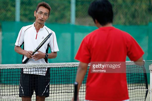 Masaki Kashiwai one of Kei Nishikori's first coaches left speaks to a boy as he gives lessons to him at Green Tennis School in Matsue Shimane...