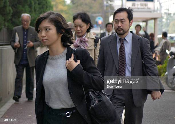 Masako Suzuki followed by Takeshi Ohashi rear right and Noriko Watanabe rear left lawyers representing representing Bobby Fischer enter the gates of...