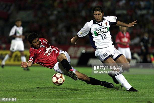 Masami Ihara of Urawa Red Diamonds and Bismarck of Kashima Antlers compete for the ball during the JLeague Yamazaki Nabisco Cup quarter final first...