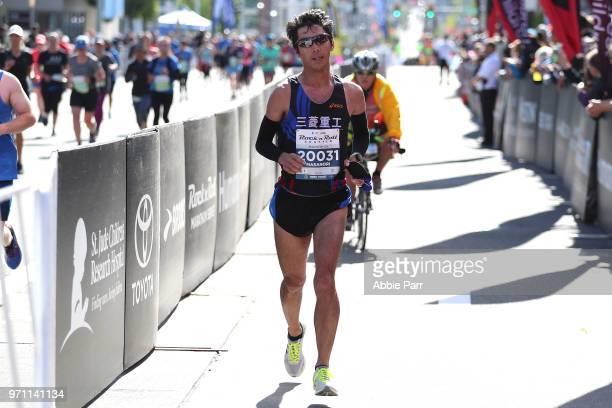 Masanori Okabe crosses the finish line to place third in the Men's Marathon during the St Jude Rock 'n' Roll Seattle Marathon 1/2 Marathon on June 10...