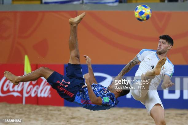 Masanori Okuyama of Japan is challenged by Nicolas Bella of Uruguay during the FIFA Beach Soccer World Cup Paraguay 2019 quarter final match between...