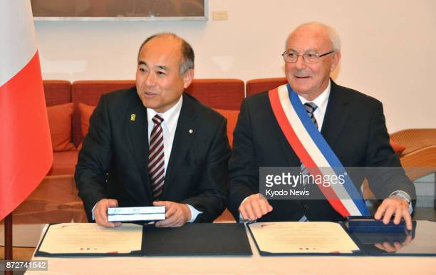 Masaomi Tokuta , mayor of Sagara, Kumamoto Prefecture in southwestern Japan, and Pierre Rousseau, mayor of Saint-Valentin, central France, attend a...