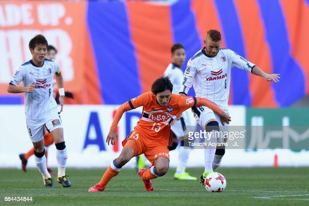 Masaru Kato of Albirex Niigata and Souza of Cerezo Osaka compete for the ball during the JLeague J1 match between Albirex Niigata and Cerezo Osaka at...