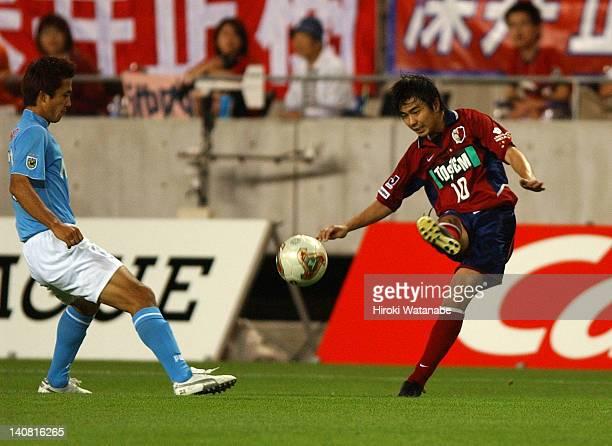 Masashi Motoyama of Kashima Antlers and Takashi Fukunishi of Jubilo Iwata compete for the ball during the JLeague match between Kashima Antlers and...