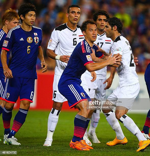 Masato Morishige and Shinji Okazaki fight for position with Ali Adnan Kadhim and Saad Abdulameer Aldobjahawe of Iraq during the first round Asian Cup...