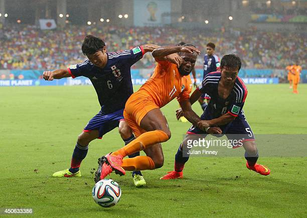 Masato Morishige and Yuto Nagatomo of Japan challenge Didier Drogba of the Ivory Coast during the 2014 FIFA World Cup Brazil Group C match between...