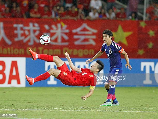 Masato Morishige of Japan looks on as Gao Lin of China controls the ball during the EAFF East Asian Cup 2015 final round at the Wuhan Sports Center...