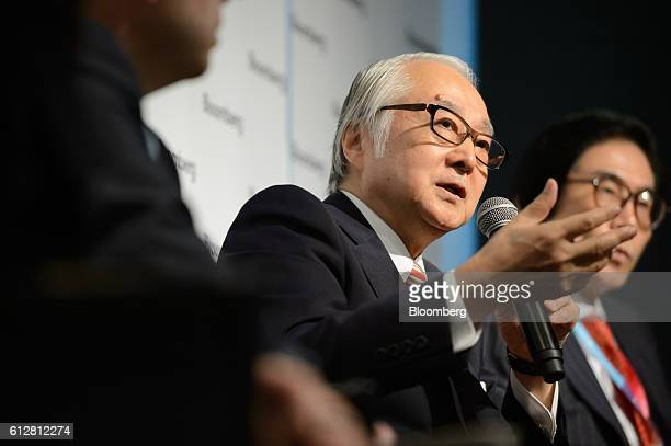 Masatsugu Nagato president and chief executive officer of Japan Post Holdings Co center gestures as he speaks as Kunio Ito special professor at...
