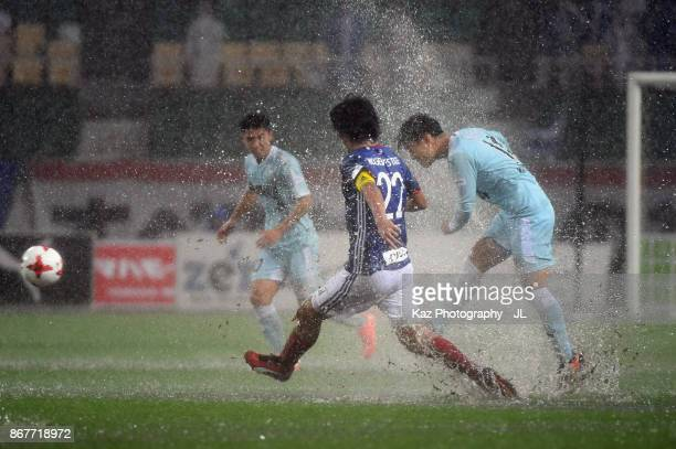 Masaya Matsumoto of Jubilo Iwata and Yuji Nakazawa of Yokohama FMarinos compete for the ball during the JLeague J1 match between Jubilo Iwata and...