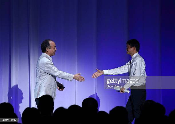 Masayoshi Son chairman and chief executive office of SoftBank Corp left and Jack Ma chairman of Alibaba Group Holding Ltd reach out to shake hands as...