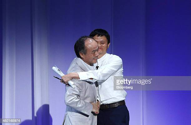 Masayoshi Son chairman and chief executive office of SoftBank Corp left hugs Jack Ma chairman of Alibaba Group Holding Ltd as Ma arrives for his...