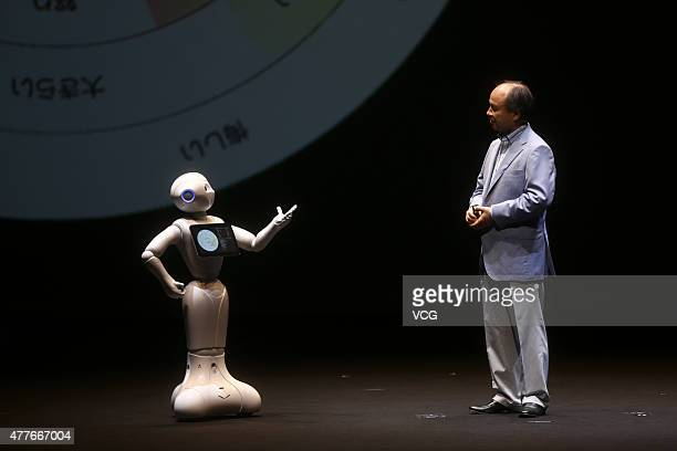 Masayoshi Son chairman and chief executive officer of SoftBank Corp talks with 'Pepper' the world's first personal robot made by Softbank during a...