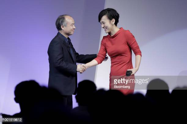 Masayoshi Son chairman and chief executive officer of SoftBank Group Corp left shakes hands with Jean Liu president of Didi Chuxing at the SoftBank...