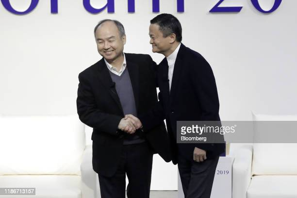 Masayoshi Son, chairman and chief executive officer of SoftBank Group Corp., left, and Jack Ma, former chairman of Alibaba Group Holding Ltd., shake...