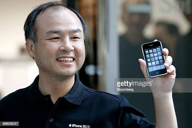 Masayoshi Son president and chief executive officer of SoftBank Corp shows the Apple Inc iPhone 3G S at SoftBank Corp's flagship store in the...