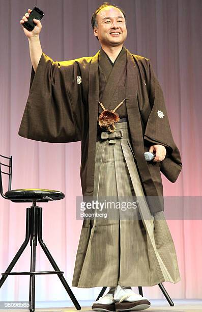 Masayoshi Son president and chief executive officer of SoftBank Corp dressed in a kimono holds up the company's HTC Desire smartphone during the...