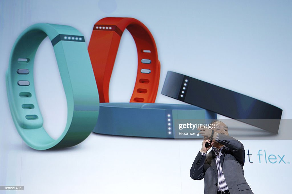 Masayoshi Son, president of SoftBank Corp., demonstrates a FitBit Inc. Fitbit Flex wearable fitness device as he introduces the company's new SoftBank HealthCare service during a product launch in Tokyo, Japan, on Tuesday, May 7, 2013. Son will visit the U.S. to meet with Sprint Nextel Corp. institutional investors to discuss the company's proposed takeover, SoftBank spokesman Mitsuhiro Kurano said today. Photographer: Kiyoshi Ota/Bloomberg via Getty Images