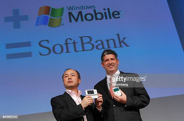 Masayoshi Son president of Softbank Corp left and Darren Huston president of Microsoft Co Japan introduce a new smartphone during a news conference...