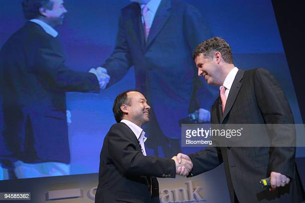 Masayoshi Son president of Softbank Corp left shakes hands with Darren Huston president of Microsoft Co Japan during a news conference in Tokyo Japan...