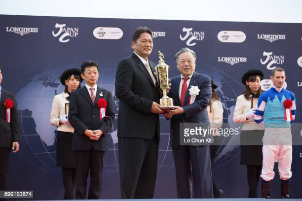 Masayuki Goto, the President and CEO of the Japan Racing Association presents the Japan Cup trophy to the owner of Cheval Grand, Kazuhiro Sasaki,...