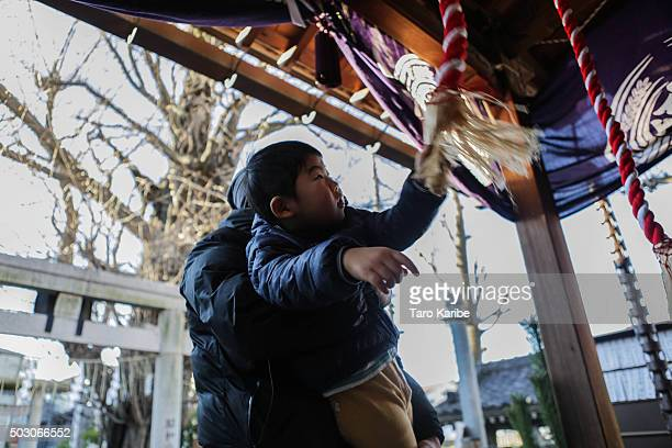 TOKYO JAPAN JANUARY 1 Masayuki Togawa 44 years old and his son Hikaru 3 years old ring the bell at the shirine on January 1 2016 in Tokyo Japan In...