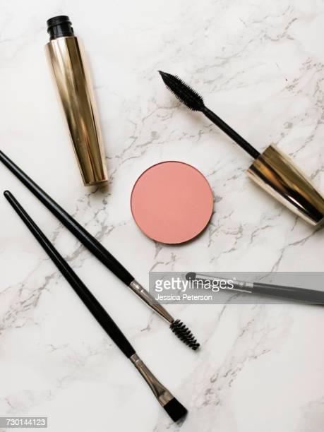 Mascara and make-up brushes on marble background