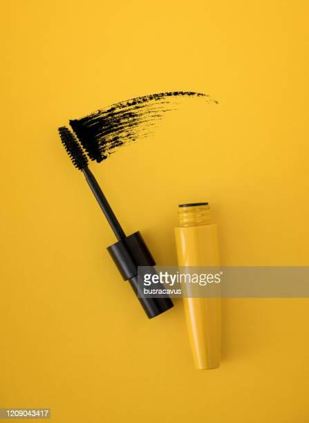 mascara brush on yellow background - mascara stock pictures, royalty-free photos & images