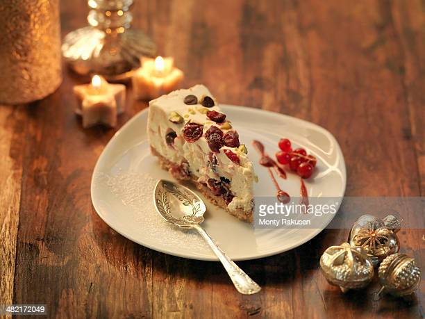 mascarpone cheesecake with cranberry, pistachio, orange zest and chocolate chip amongst festive decorations - christmas cake stock photos and pictures