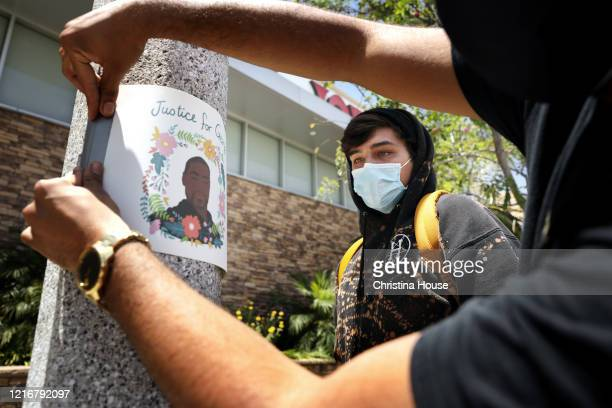 Mascelys Luna right and Kyle Stanaway center both of Beverly Hills post signs that read 'Justice for George' around the Fairfax District on Sunday...