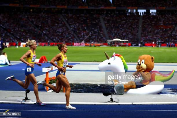 Mascot Berlino floats in the steeplechase water jump as athletes compete in the Women's 5000 metres during day six of the 24th European Athletics...