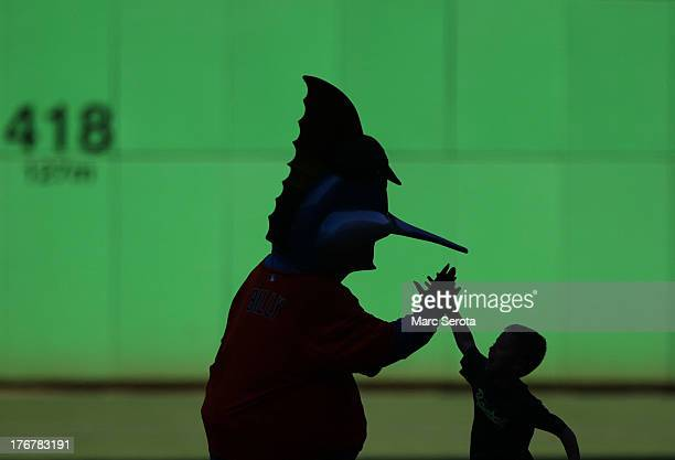 Mascot 'Billy the Marlin' greets a young fan as he runs the bases during post game diamond dash after the Miami Marlins played against the San...