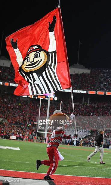 Mascot Brutus the Buckeye runs on the field with a flag after a Ohio State touchdown during a game between the Ohio State Buckeyes and the Penn State...