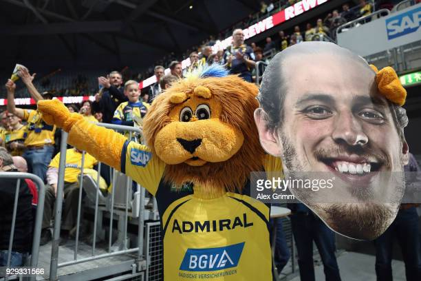 Mascot Conny poses with a huge print out of the face of Loewen player Kim Ekdahl du Rietz after the DHL HBL match between RheinNeckar Loewen and...
