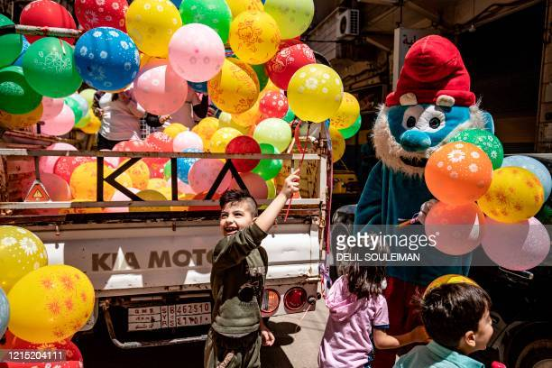 TOPSHOT A mascot dressed as a Smurf hands balloons to children during the Muslim Eid alFitr holiday as part of a local NGO awareness campaign to...
