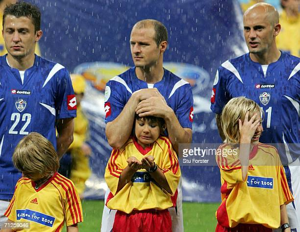 A mascot gets protected from the rain by Igor Duljaj of Serbia Montenegro before the start of the FIFA World Cup Germany 2006 match between Ivory...