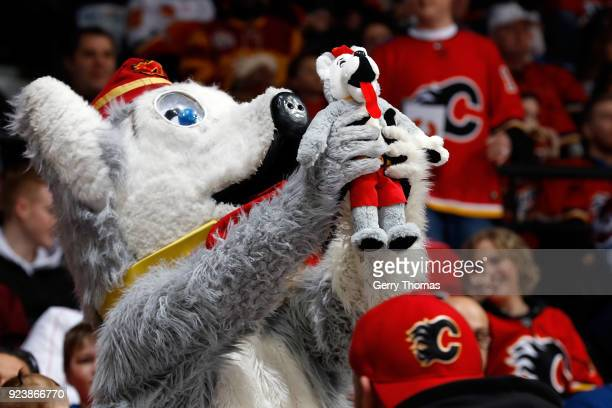 Mascot Harvey the Hound holds up his own plush doll during an NHL game between the Calgary Flames and the Colorado Avalanche on February 24 2018 at...