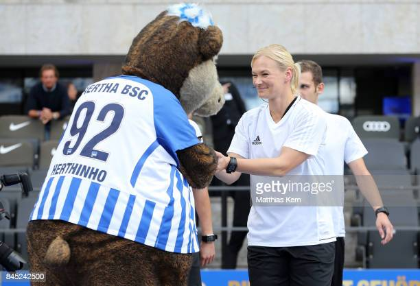 Mascot Herthinho of Berlin greets Referee Bibiana Steinhaus prior to the Bundesliga match between Hertha BSC and SV Werder Bremen at Olympiastadion...