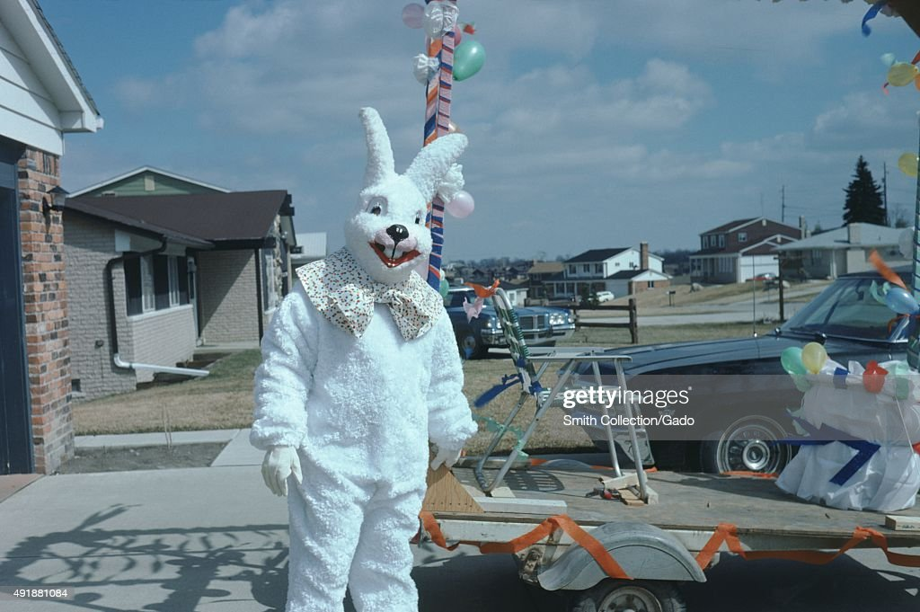 Mascot in a large white rabbit costume, standing in the driveway of a suburban home, a lawn chair on a flatbed trailer with bunting and balloons, before a parade, 1975.