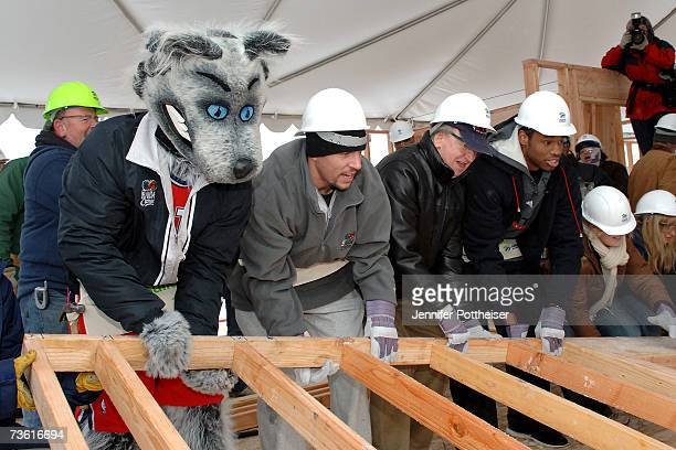 Mascot Sly Fox Jason Kidd Rod Thorn and Jason Collins of the New Jersey Nets help to build a house for Habitat for Humanity March 16 2007 in East...