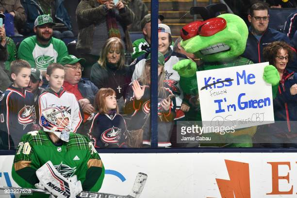Mascot Stinger waves to goaltender Joonas Korpisalo of the Columbus Blue Jackets during warm ups before a game against the Ottawa Senators on March...