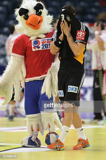 Mascot Tasa and Uwe Gensheimer of Germany look dejected after losing 3233 the Men's European Handball Championship second round group one match...
