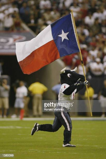 Mascot Toro of the Houston Texans runs with the Texas state flag during the NFL game against the Dallas Cowboys on September 8 2002 at Reliant...