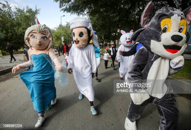Mascots participate with young Iraqis in the first children's marathon run in the capital Baghdad on December 7 2018