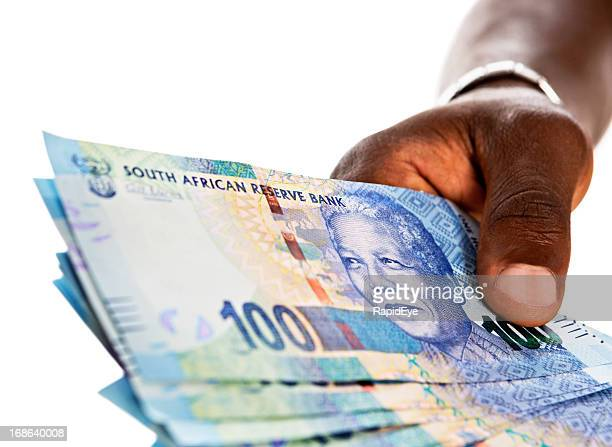 masculine hand holds out bundle of hundred rand banknotes - south african currency stock photos and pictures