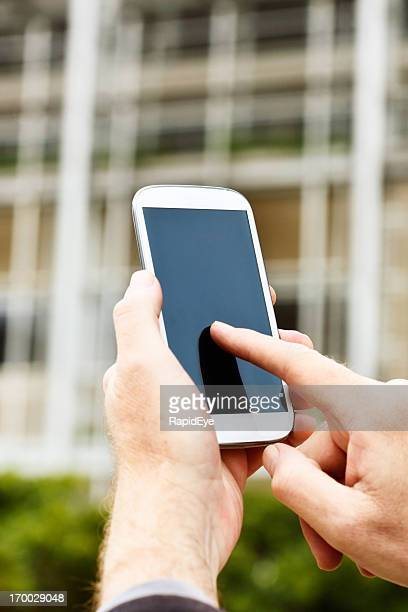 Masculine hand tapping touch screen of smart phone outside building