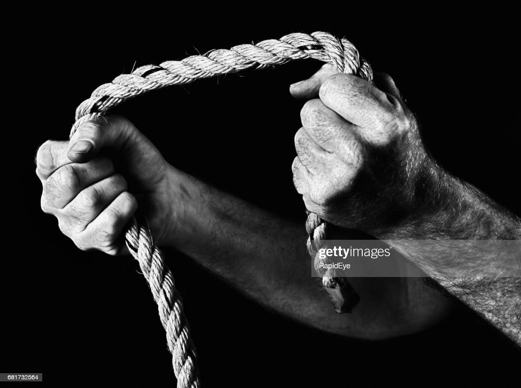 Masculine hands grip rope, pulling apart. Black and white. : Stock Photo