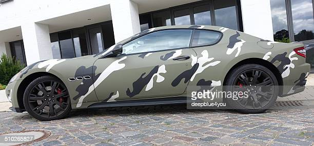 maserati in camouflage color, outdoor on parking lot - maserati stock photos and pictures