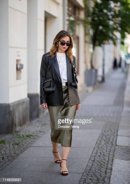 Masha Sedgwick is seen wearing black leather blazer 8 by yoxx bag vest Liebeskund Proenza Schouler heels white Jacquemus shirt olive green silk midi...
