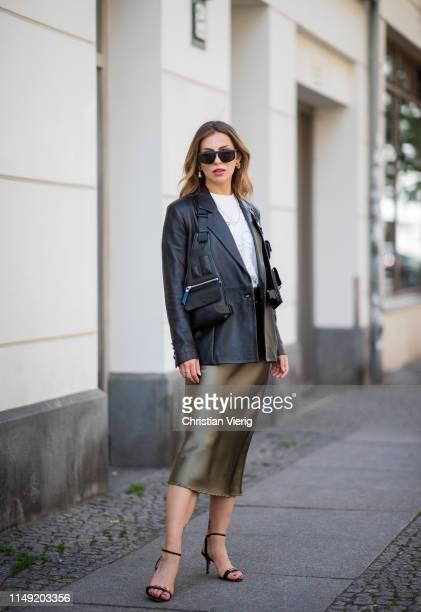 Masha Sedgwick is seen wearing black leather blazer 8 by yoxx, bag vest Liebeskund, Proenza Schouler heels, white Jacquemus shirt, olive green silk...
