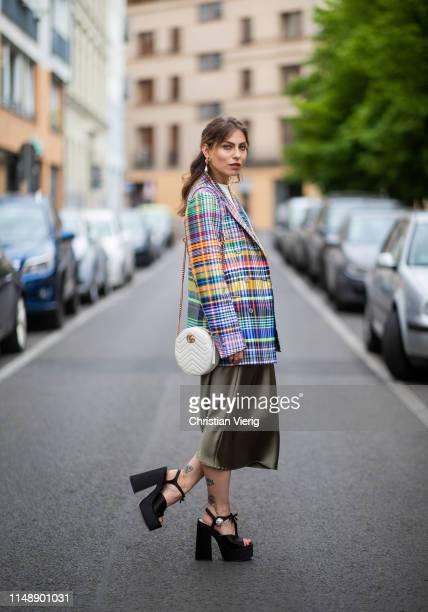 Masha Sedgwick is seen wearing checked multi colored blazer Dries van Noten, green silk Topshop midi skirt, Miu Miu high plateau sandals, white round...